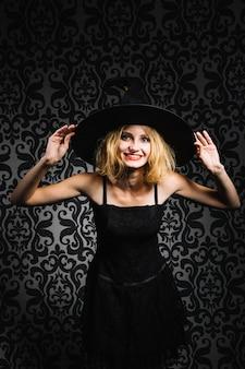 Bruxa, menina, segurando, chapéu, sorrindo