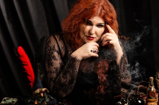 Bruxa mulher, cartomante com cabelo vermelho executa um ritual mágico.