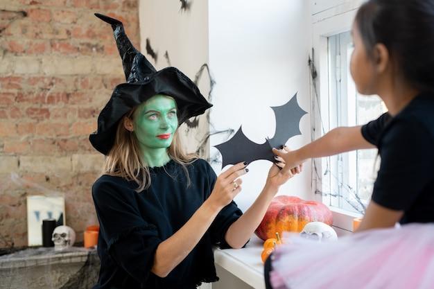 Bruxa mulher com maquiagem verde dando papel de rato para a garota enquanto elas decoram o quarto juntas para o halloween