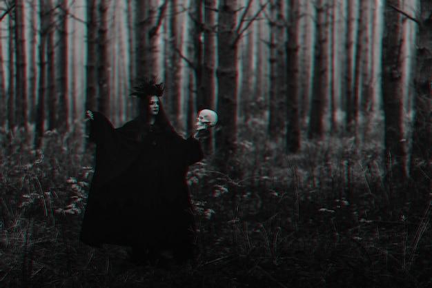Bruxa negra terrível com uma caveira nas mãos de um homem morto realiza um ritual místico oculto. preto e branco com efeito de realidade virtual de falha 3d