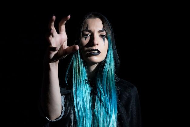 Bruxa no capuz com cabelo turquesa
