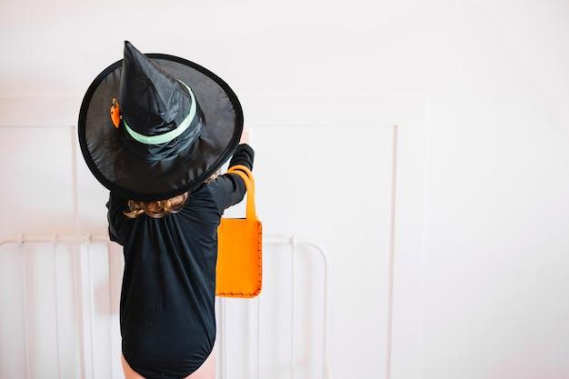 Bruxa pequena com saco de laranja perto da cabeceira