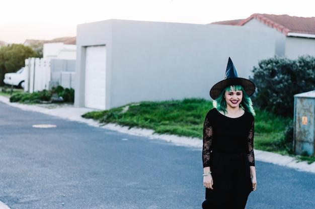 Bruxa sorridente na rua suburbana