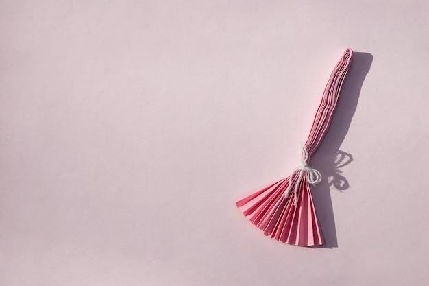Bruxaria de papel rosa sobre fundo rosa. fundo criativo de halloween com espaço de cópia.