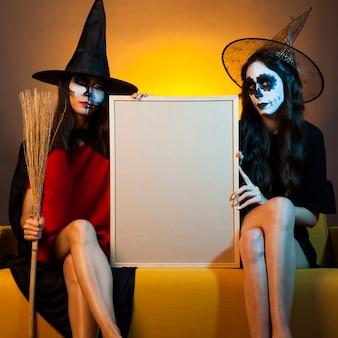 Bruxas no sofá segurando quadro branco