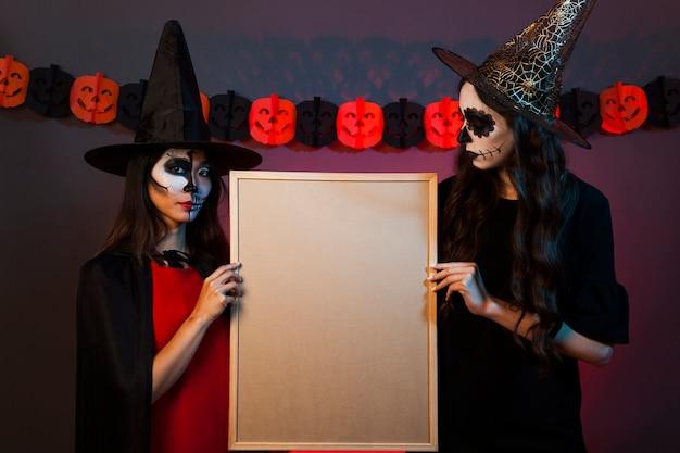 Bruxas segurando quadro branco