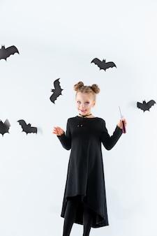 Bruxinha de vestido longo preto e acessórios mágicos. dia das bruxas