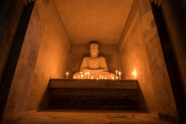 Buda com velas brilhantes em uma parede de tijolos.