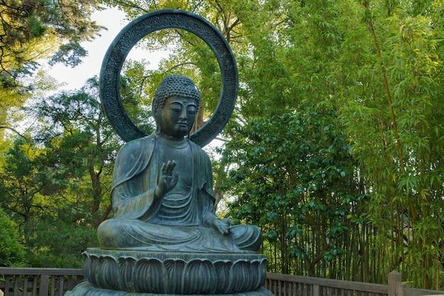 Buda de bronze sentado no jardim japonês