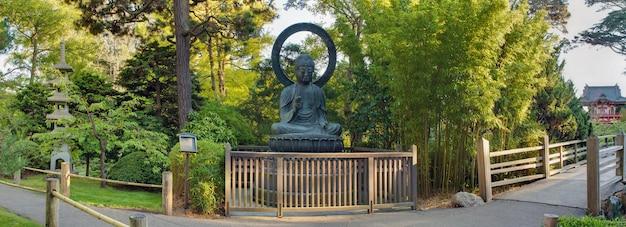 Buda de bronze sentado no panorama do jardim japonês