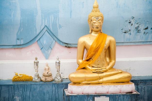 Buda dourado com tecido amarelo e pequenas peças fechadas contra a parede do templo na tailândia em koh samui