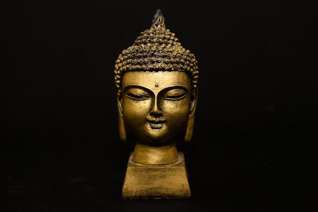 Buda dourado e fundo preto Foto Premium