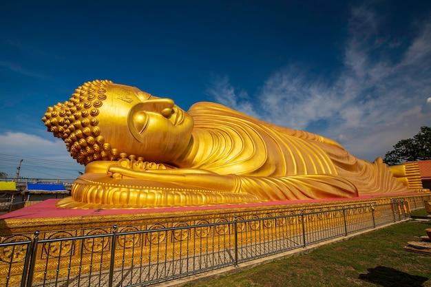 Buda reclinado de ouro buda, a estátua do senhor no templo budista no céu azul da tailândia
