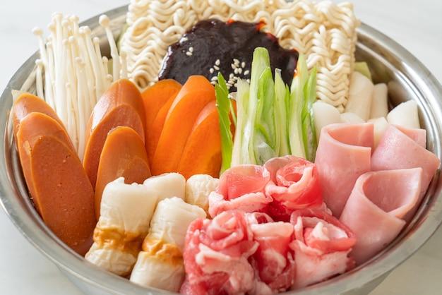 Budae jjigae ou budaejjigae (guisado do exército ou guisado da base do exército). é carregado com kimchi, spam, linguiças, macarrão ramen