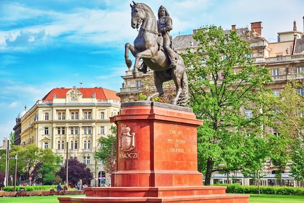 Budapeste, hungria-2 de maio de 2016: monumento para francis ii rakoczi à esquerda do edifício do parlamento húngaro, na praça lajos kossuth, em budapeste. hungria.