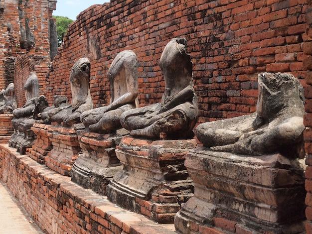 Buddha com a parede de tijolo velha ayutthaya, tailândia
