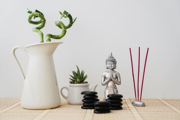 Buddha figura com pedras pretas, incenso e vegetação
