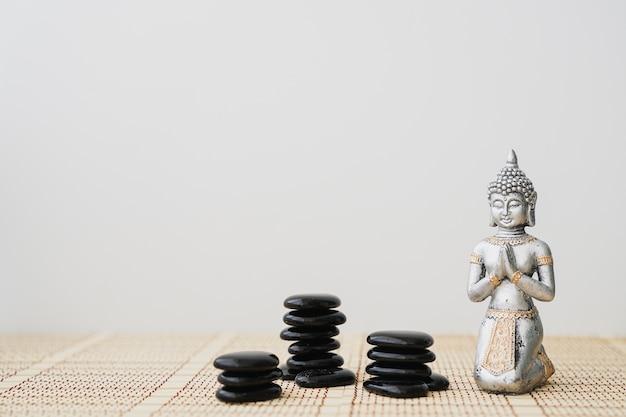 Buddha figura com pedras pretas