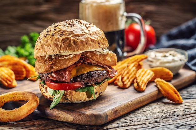 Budrger de carne com queijo duplo, rodelas de batata, anel de cebola, tomate, maionese e uma cerveja escura no fundo.