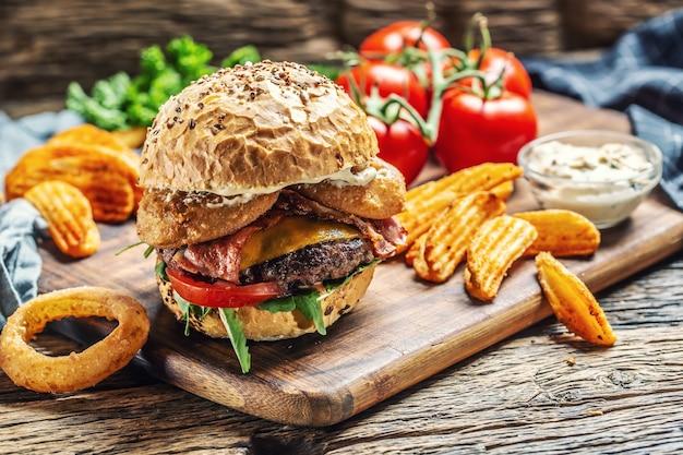 Budrger de carne com queijo duplo, rodelas de batata, anel de cebola, tomate, maionese em uma tábua escura.