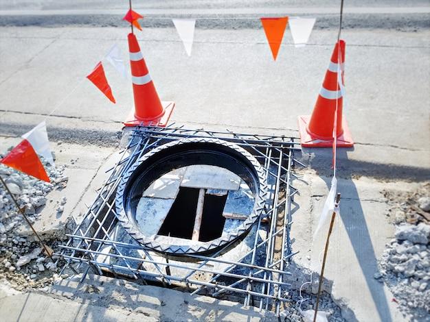 Bueiro de esgoto redondo em construção com cones de estrada como barricada de aviso