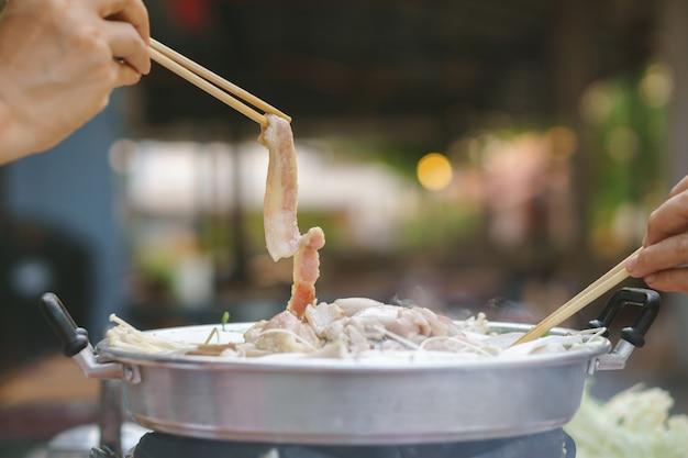 Buffet comum tailandês, grelhados de porco ou churrasco na panela quente