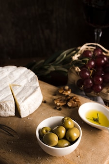 Buffet de alto ângulo delicioso com queijo e azeitonas na placa de madeira