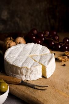Buffet de alto ângulo delicioso com queijo na placa de madeira