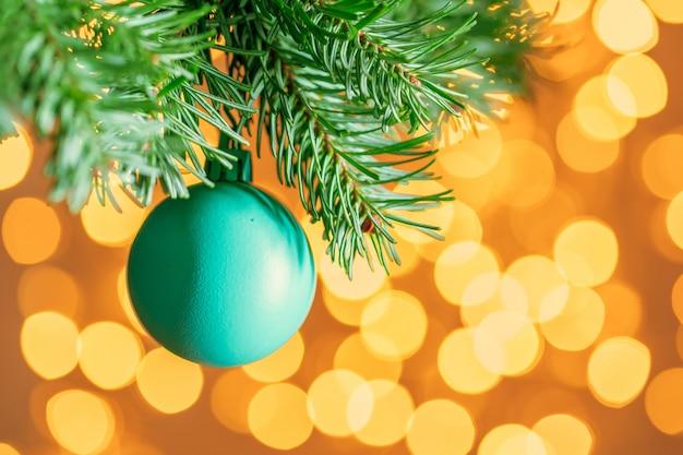 Bugiganga azul pendurado em um galho de árvore do abeto contra bokeh dourado