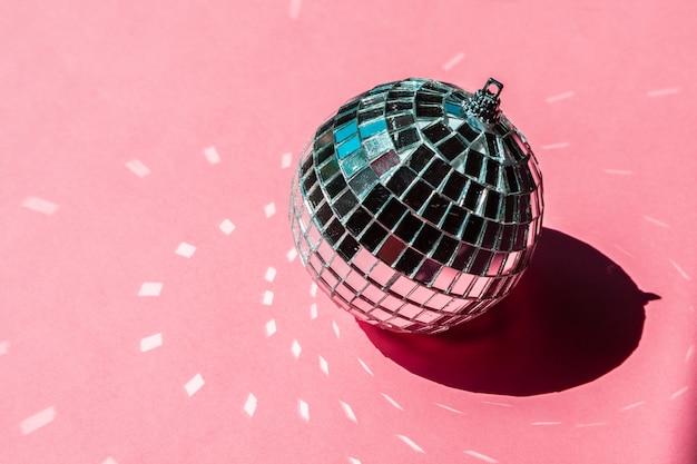 Bugiganga bola de discoteca em fundo rosa. festa