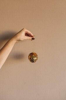 Bugiganga dourada brilhante espumante em mulheres mão bege.