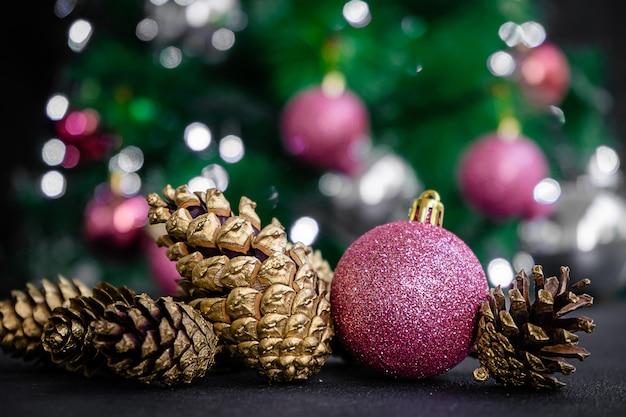 Bugiganga roxa e pinhas coloridas douradas no fundo desfocado da árvore de natal