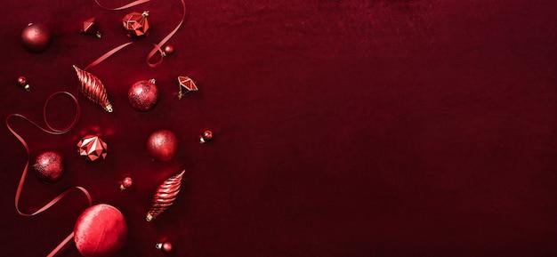 Bugiganga vermelha de decoração de natal e fita em tecido de feltro vermelho de veludo vista superior da mesa de fundo