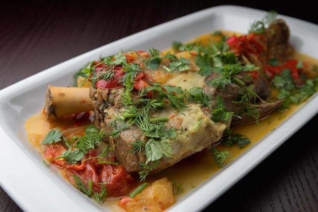 Buglama do azerbaijão, num prato branco com ervas e molho