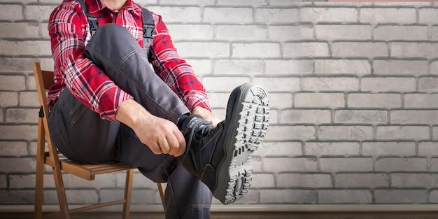 Buider calçar sapatos para trabalhar perto da parede de tijolos. trabalho de segurança. bandeira.