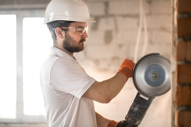 Builder trabalha com uma rebarbadora profissional para cortar tijolos