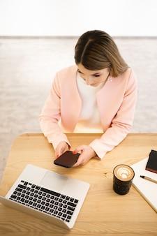 Buinesswoman com sorriso sincero, conversando por telefone e aproveitando a pausa para o café no café. vestindo um casaco casual branco rosa jaket