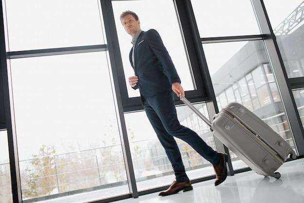 Buisnessman confiante jovem andando pelo corredor. ele tem bagagem. o homem está no aeroporto.