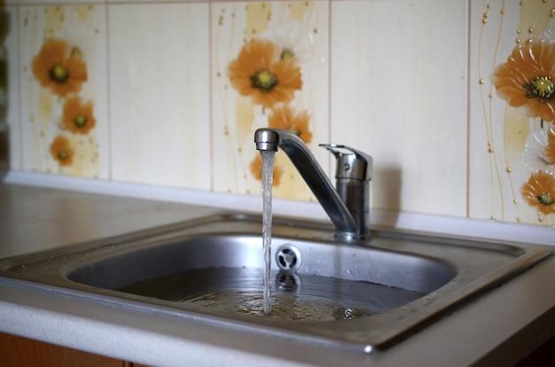 Bujão de pia de aço inoxidável fechar cheio de água e partículas de alimentos