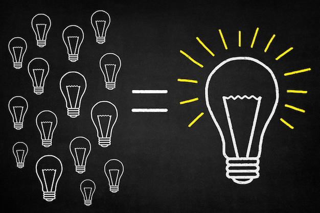 Bulbo branco desenhado em um quadro-negro com outras lâmpadas perto