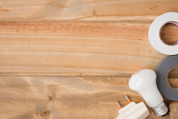Bulbo branco; fita isolante e botão sobre a mesa de madeira