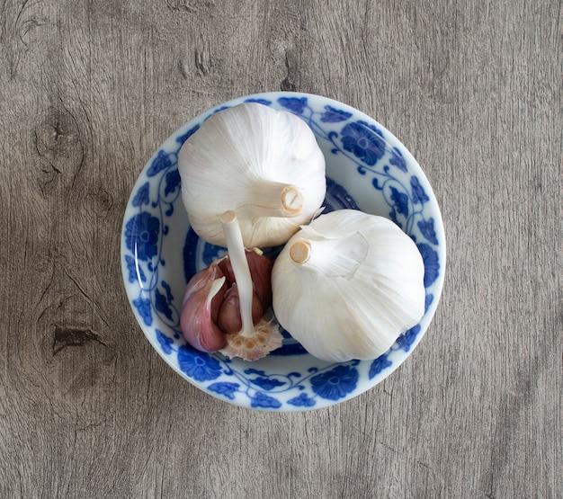 Bulbo de alho e cravo em uma tigela branca e azul vintage decorado sobre fundo de madeira