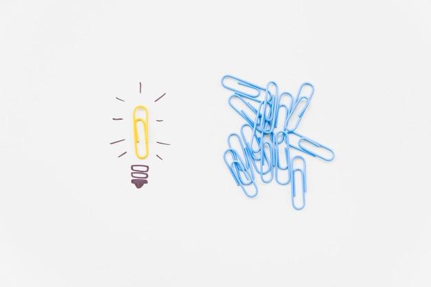 Bulbo de desenho com clipe de papel amarelo como luz