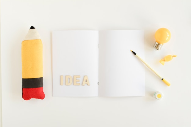 Bulbo elétrico, doces, lápis com texto de ideia no cartão