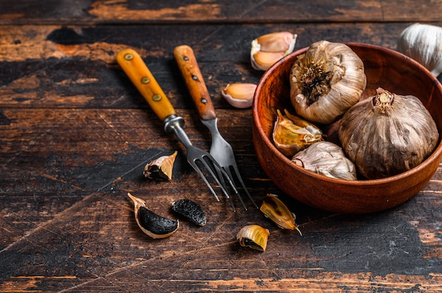 Bulbos e dentes de alho preto fermentado em um prato