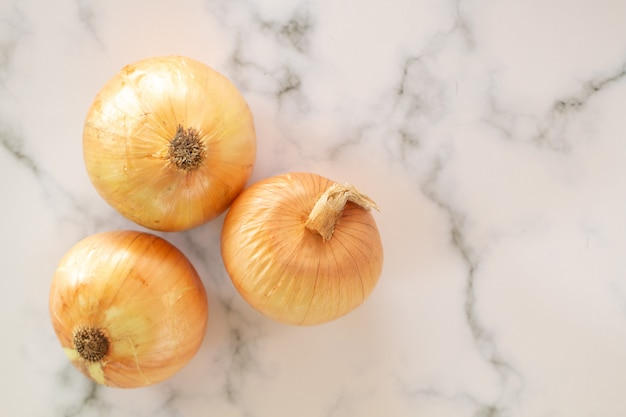 Bulbos frescos de cebola na mesa de mármore