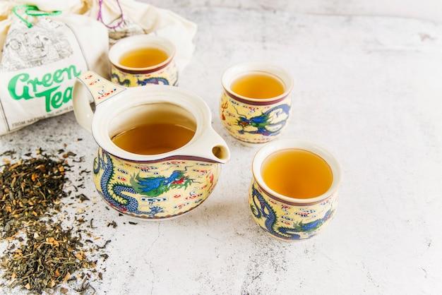 Bule antigo tradicional com xícaras e chá de ervas secas em fundo de concreto