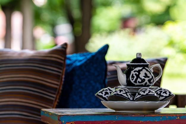 Bule com canecas close-up sobre uma mesa na varanda do jardim, foco seletivo