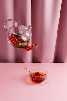 Bule com chá de frutas vermelhas levitando acima da xícara