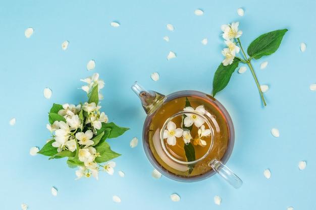 Bule com chá de jasmim e flores de jasmim em uma superfície azul. uma bebida revigorante que faz bem à saúde.